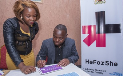 "A journalist, Harold Kapindu signs the HE FOR SHE campaign form in support of gender equality as UN Women volunteer, Hope Matilda Mawerenga, watches during the premiere of ""Mercy's Blessing""."